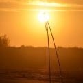 Makeshift tripod on beach with setting sun